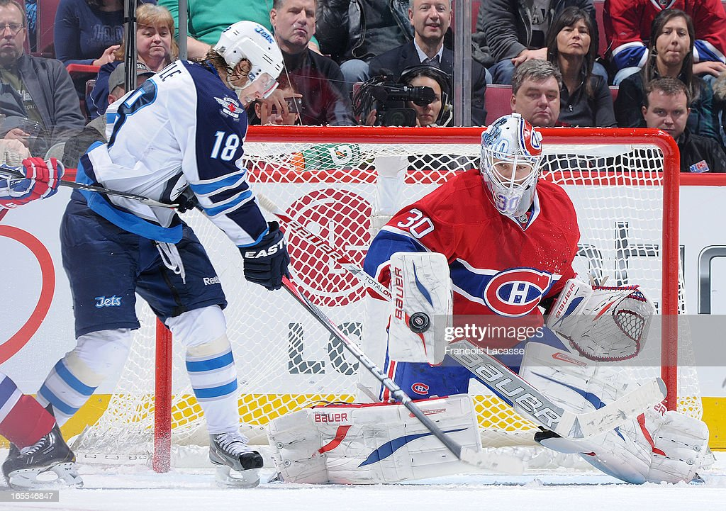 Goalie <a gi-track='captionPersonalityLinkClicked' href=/galleries/search?phrase=Peter+Budaj&family=editorial&specificpeople=228123 ng-click='$event.stopPropagation()'>Peter Budaj</a> #30 of the Montreal Canadiens makes a blocker save against <a gi-track='captionPersonalityLinkClicked' href=/galleries/search?phrase=Bryan+Little&family=editorial&specificpeople=540533 ng-click='$event.stopPropagation()'>Bryan Little</a> #18 of the Winnipeg Jets during the NHL game on April 4, 2013 at the Bell Centre in Montreal, Quebec, Canada.