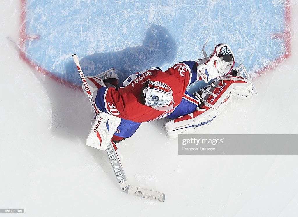 Goalie Peter Budaj #30 of the Montreal Canadiens makes a glove save during warm ups prior to the NHL game against the New York Rangers on March 30, 2013 at the Bell Centre in Montreal, Quebec, Canada.