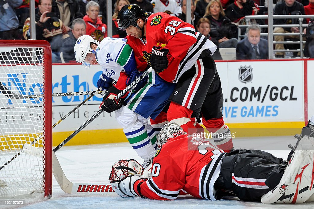 Goalie Ray Emery #30, Michal Rozsival #32 of the Chicago Blackhawks and Henrik Sedin #33 of the Vancouver Canucks fight over the puck during the NHL game on February 19, 2013 at the United Center in Chicago, Illinois.