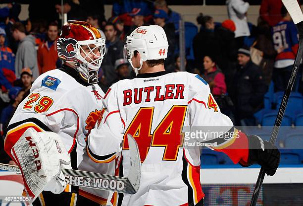 Goalie Reto Berra and Chris Butler of the Calgary Flames celebrate their victory after an NHL hockey game against the New York Islanders at Nassau...