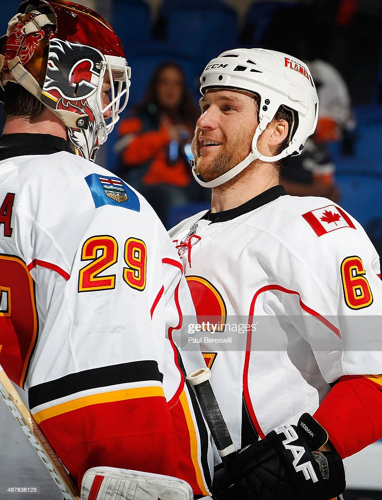 Goalie Reto Berra #29 and Dennis Wideman #6 of the Calgary Flames celebrate their victory after an NHL hockey game against the New York Islanders at Nassau Veterans Memorial Coliseum on February 6, 2014 in Uniondale, New York.
