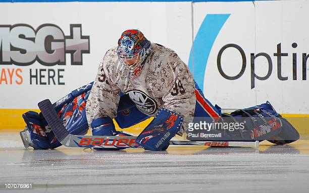 Goalie Rick DiPietro of the New York Islanders stretches during practice wearing a military style jersey in honor of military night before a hockey...