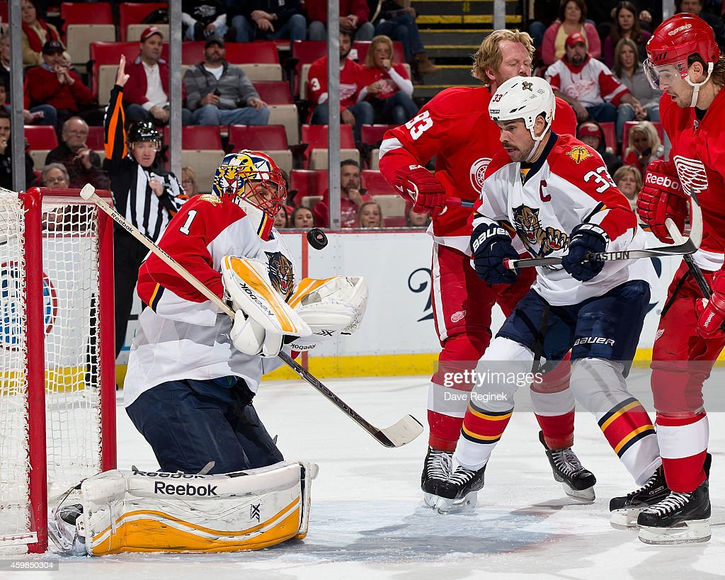 Goalie <a gi-track='captionPersonalityLinkClicked' href=/galleries/search?phrase=Roberto+Luongo&family=editorial&specificpeople=202638 ng-click='$event.stopPropagation()'>Roberto Luongo</a> #1 of the Florida Panthers makes a save as teammate Willie Mitchell #33 battles with <a gi-track='captionPersonalityLinkClicked' href=/galleries/search?phrase=Johan+Franzen&family=editorial&specificpeople=624356 ng-click='$event.stopPropagation()'>Johan Franzen</a> #93 and Brendan Smith #2 of the Detroit Red Wings during a NHL game on December 2, 2014 at Joe Louis Arena in Detroit, Michigan.