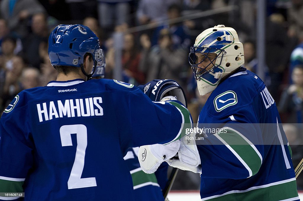Goalie <a gi-track='captionPersonalityLinkClicked' href=/galleries/search?phrase=Roberto+Luongo&family=editorial&specificpeople=202638 ng-click='$event.stopPropagation()'>Roberto Luongo</a> #1 of the Vancouver Canucks is congratulated by <a gi-track='captionPersonalityLinkClicked' href=/galleries/search?phrase=Dan+Hamhuis&family=editorial&specificpeople=204213 ng-click='$event.stopPropagation()'>Dan Hamhuis</a> #2 after defeating the Minnesota Wild 2-1 in NHL action on February 12, 2013 at Rogers Arena in Vancouver, British Columbia, Canada.