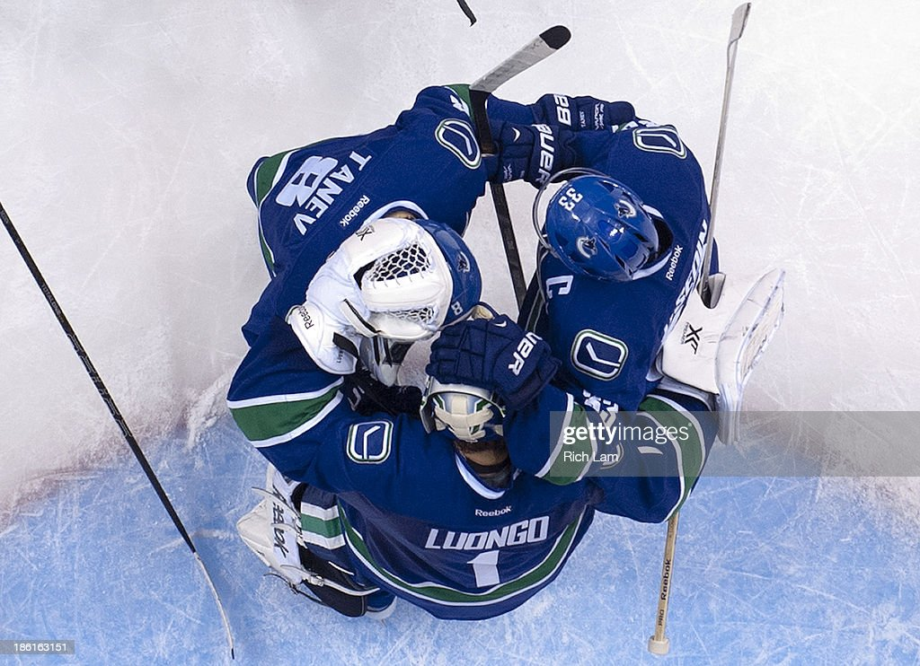 Goalie <a gi-track='captionPersonalityLinkClicked' href=/galleries/search?phrase=Roberto+Luongo&family=editorial&specificpeople=202638 ng-click='$event.stopPropagation()'>Roberto Luongo</a> #1 of the Vancouver Canucks is congratulated by teammates Chris Tanev #8 and <a gi-track='captionPersonalityLinkClicked' href=/galleries/search?phrase=Henrik+Sedin&family=editorial&specificpeople=202574 ng-click='$event.stopPropagation()'>Henrik Sedin</a> #33 after defeating the Washington Capitals 3-2 in NHL action on October 28, 2013 at Rogers Arena in Vancouver, British Columbia, Canada.