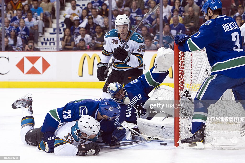 Goalie <a gi-track='captionPersonalityLinkClicked' href=/galleries/search?phrase=Roberto+Luongo&family=editorial&specificpeople=202638 ng-click='$event.stopPropagation()'>Roberto Luongo</a> #1 of the Vancouver Canucks keeps the puck out of the net while <a gi-track='captionPersonalityLinkClicked' href=/galleries/search?phrase=Alexander+Edler&family=editorial&specificpeople=882987 ng-click='$event.stopPropagation()'>Alexander Edler</a> #23 of the Canucks and <a gi-track='captionPersonalityLinkClicked' href=/galleries/search?phrase=Raffi+Torres&family=editorial&specificpeople=204612 ng-click='$event.stopPropagation()'>Raffi Torres</a> #13 of the San Jose Sharks fall to the ice in the third period of Game Two of the Western Conference Quarterfinals of the 2013 NHL Stanley Cup Playoffs, May 03, 2013 at Rogers Arena in Vancouver, British Columbia, Canada. <a gi-track='captionPersonalityLinkClicked' href=/galleries/search?phrase=Logan+Couture&family=editorial&specificpeople=809700 ng-click='$event.stopPropagation()'>Logan Couture</a> #39 of the San Jose Sharks and <a gi-track='captionPersonalityLinkClicked' href=/galleries/search?phrase=Kevin+Bieksa&family=editorial&specificpeople=688792 ng-click='$event.stopPropagation()'>Kevin Bieksa</a> #3 of the Vancouver Canucks look on during the play.
