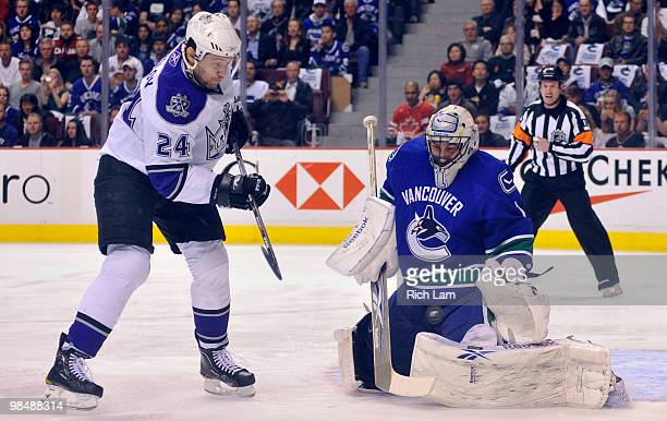 Goalie Roberto Luongo of the Vancouver Canucks makes a pad save while Alexander Frolov of the Los Angeles Kings looks for a rebound in Game One of...