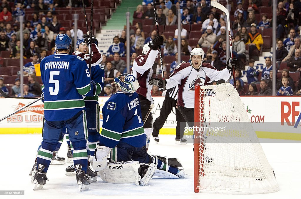 Goalie <a gi-track='captionPersonalityLinkClicked' href=/galleries/search?phrase=Roberto+Luongo&family=editorial&specificpeople=202638 ng-click='$event.stopPropagation()'>Roberto Luongo</a> #1 of the Vancouver Canucks reacts after <a gi-track='captionPersonalityLinkClicked' href=/galleries/search?phrase=Jamie+McGinn&family=editorial&specificpeople=537964 ng-click='$event.stopPropagation()'>Jamie McGinn</a> #11 of the Colorado Avalanche scored a last minute goal to break the shutout during the third period in NHL action on December 08, 2013 at Rogers Arena in Vancouver, British Columbia, Canada. <a gi-track='captionPersonalityLinkClicked' href=/galleries/search?phrase=Cody+McLeod&family=editorial&specificpeople=2242985 ng-click='$event.stopPropagation()'>Cody McLeod</a> #55, and John Mitchell #7 of the Colorado Avalanche celebrates while <a gi-track='captionPersonalityLinkClicked' href=/galleries/search?phrase=Jason+Garrison&family=editorial&specificpeople=2143635 ng-click='$event.stopPropagation()'>Jason Garrison</a> #5 of the Vancouver Canucks looks on.