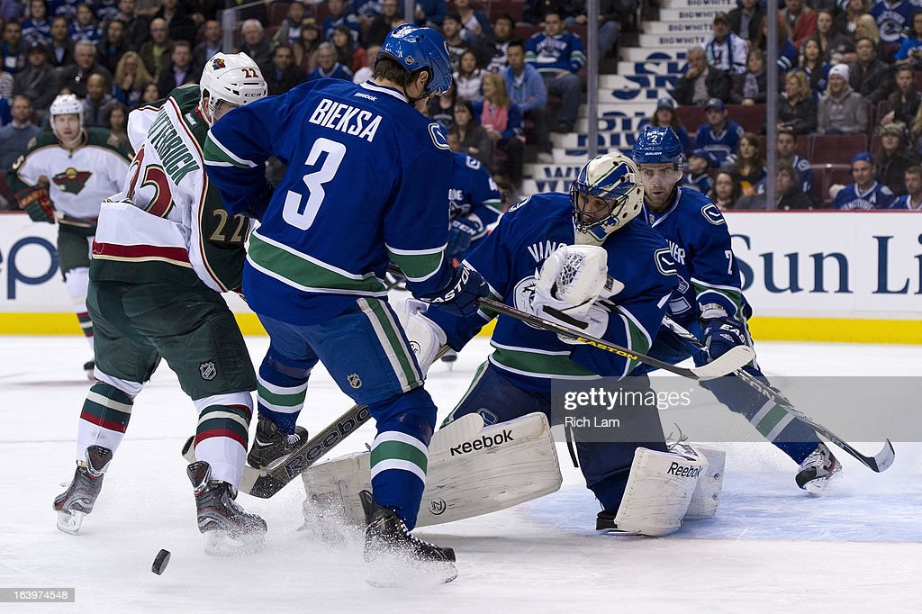 Goalie Roberto Luongo #1 of the Vancouver Canucks scrambles to make a save while Cal Clutterbuck #22 of the Minnesota Wild and Kevin Bieksa #3 of the Vancouver Canucks battle in front of the net during the first period in NHL action on March 18, 2013 at Rogers Arena in Vancouver, British Columbia, Canada. Dan Hamhuis #2 of the Vancouver Canucks looks on in the background.