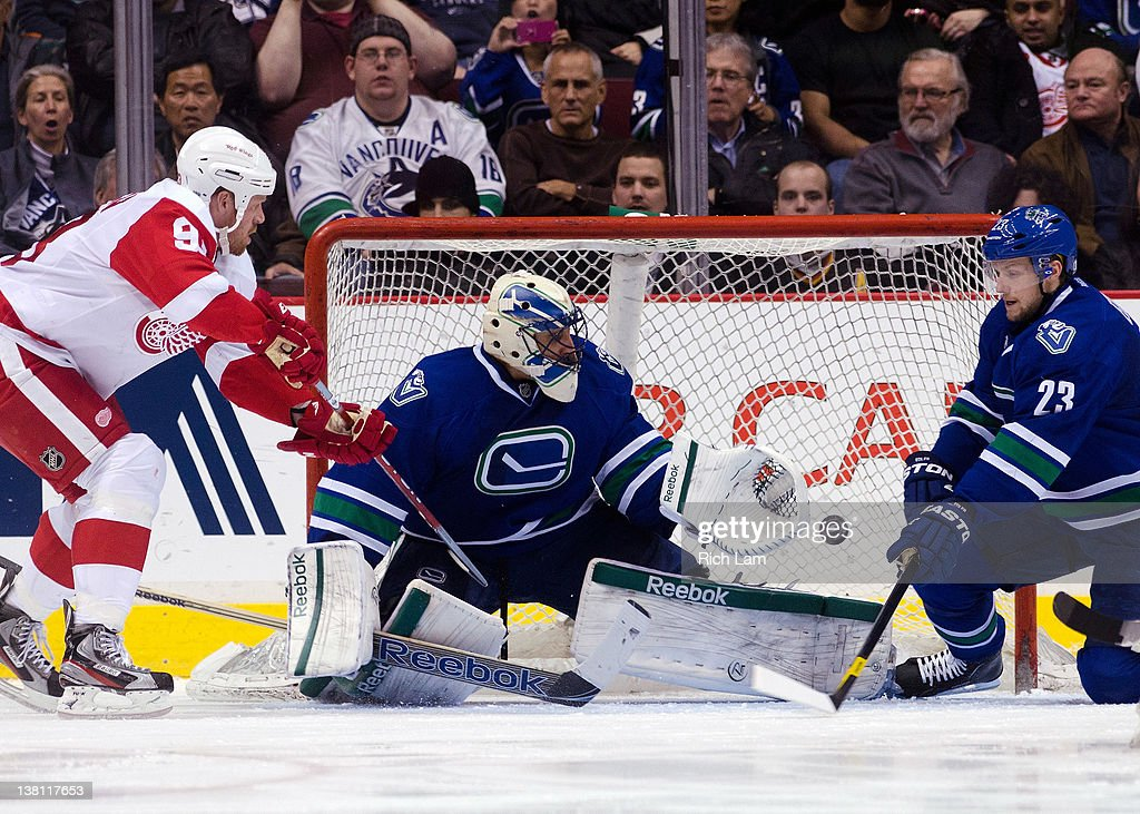 Goalie <a gi-track='captionPersonalityLinkClicked' href=/galleries/search?phrase=Roberto+Luongo&family=editorial&specificpeople=202638 ng-click='$event.stopPropagation()'>Roberto Luongo</a> #1 of the Vancouver Canucks slides across his crease to make a save as <a gi-track='captionPersonalityLinkClicked' href=/galleries/search?phrase=Johan+Franzen&family=editorial&specificpeople=624356 ng-click='$event.stopPropagation()'>Johan Franzen</a> #93 of the Detroit Red Wings and <a gi-track='captionPersonalityLinkClicked' href=/galleries/search?phrase=Alexander+Edler&family=editorial&specificpeople=882987 ng-click='$event.stopPropagation()'>Alexander Edler</a> #23 of the Vancouver Canucks look on during the second period in NHL action on February 02, 2012 at Rogers Arena in Vancouver, British Columbia, Canada.