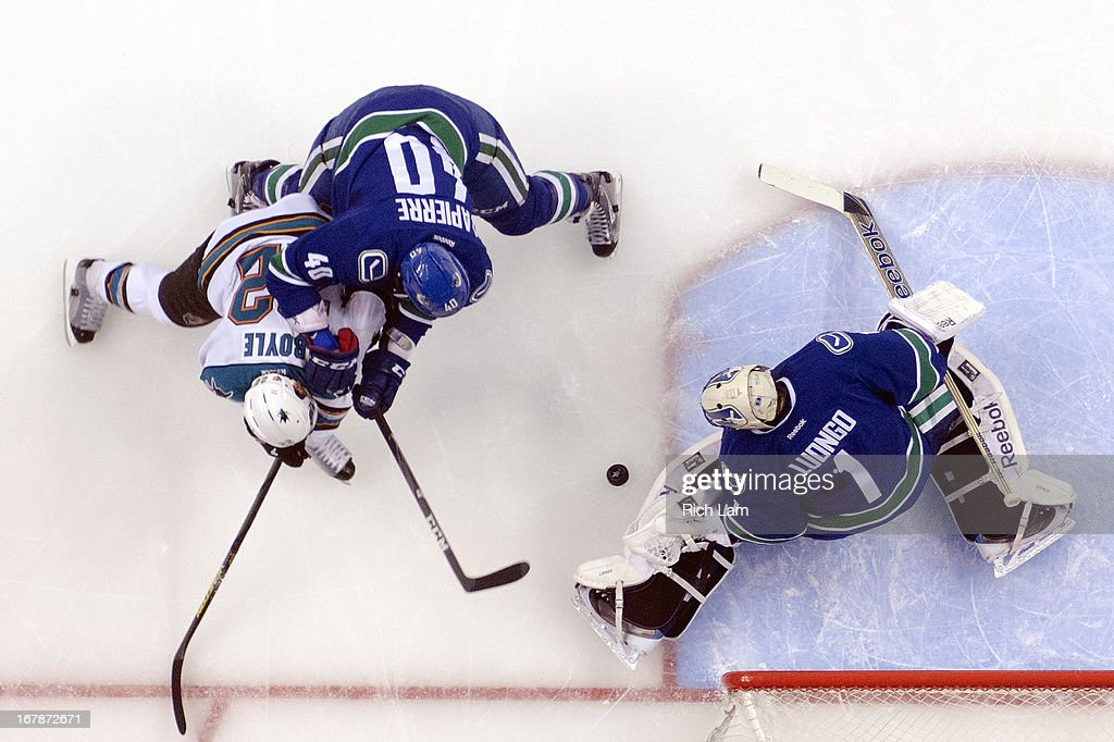 Goalie <a gi-track='captionPersonalityLinkClicked' href=/galleries/search?phrase=Roberto+Luongo&family=editorial&specificpeople=202638 ng-click='$event.stopPropagation()'>Roberto Luongo</a> #1 of the Vancouver Canucks stops <a gi-track='captionPersonalityLinkClicked' href=/galleries/search?phrase=Dan+Boyle&family=editorial&specificpeople=201502 ng-click='$event.stopPropagation()'>Dan Boyle</a> #22 of the San Jose Sharks during the second period in Game One of the Western Conference Quarterfinals of the 2013 NHL Stanley Cup Playoffs, May 01, 2013 at Rogers Arena in Vancouver, British Columbia, Canada. <a gi-track='captionPersonalityLinkClicked' href=/galleries/search?phrase=Maxim+Lapierre&family=editorial&specificpeople=718385 ng-click='$event.stopPropagation()'>Maxim Lapierre</a> #40 of the Vancouver Canucks tries to help defend on the play.