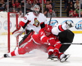 Goalie Robin Lehner of the Ottawa Senators looks over teammate Mika Zibanejad as he goes to the ice with Daniel Cleary of the Detroit Red Wings...