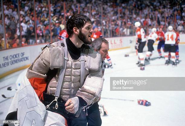Goalie Ron Hextall of the Philadelphia Flyers is escorted to the bench after being in a fight during the game against the Montreal Canadiens on...