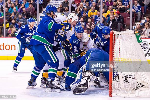 Goalie Ryan Miller dives for a lose puck as Left Wing Daniel Sedin Defenceman Troy Stecher and Vancouver Canucks Defenceman Luca Sbisa defends...