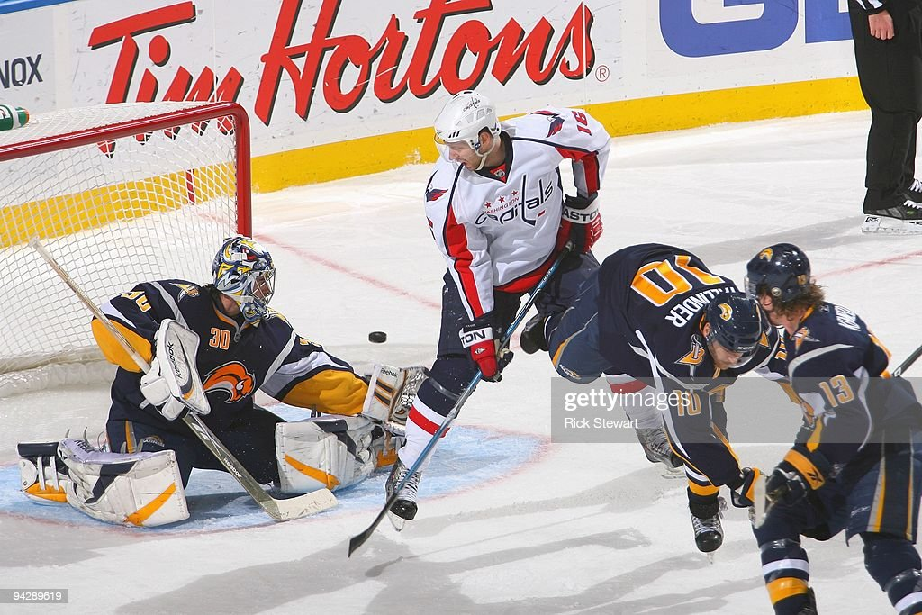 Goalie Ryan Miller of the Buffalo Sabres deflects the puck against Eric Fehr of the Washington Capitals on December 9 2009 at HSBC Arena in Buffalo...