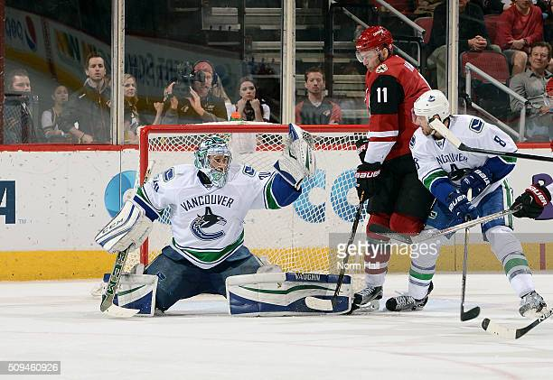 Goalie Ryan Miller of the Vancouver Canucks makes a glove save in front of teammate Christopher Tanev and Martin Hanzal of the Arizona Coyotes during...