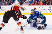 Goalie Ryan Miller of the Vancouver Canucks stops Mason Raymond of the Calgary Flames in close in NHL action on October 10 2015 at Rogers Arena in...