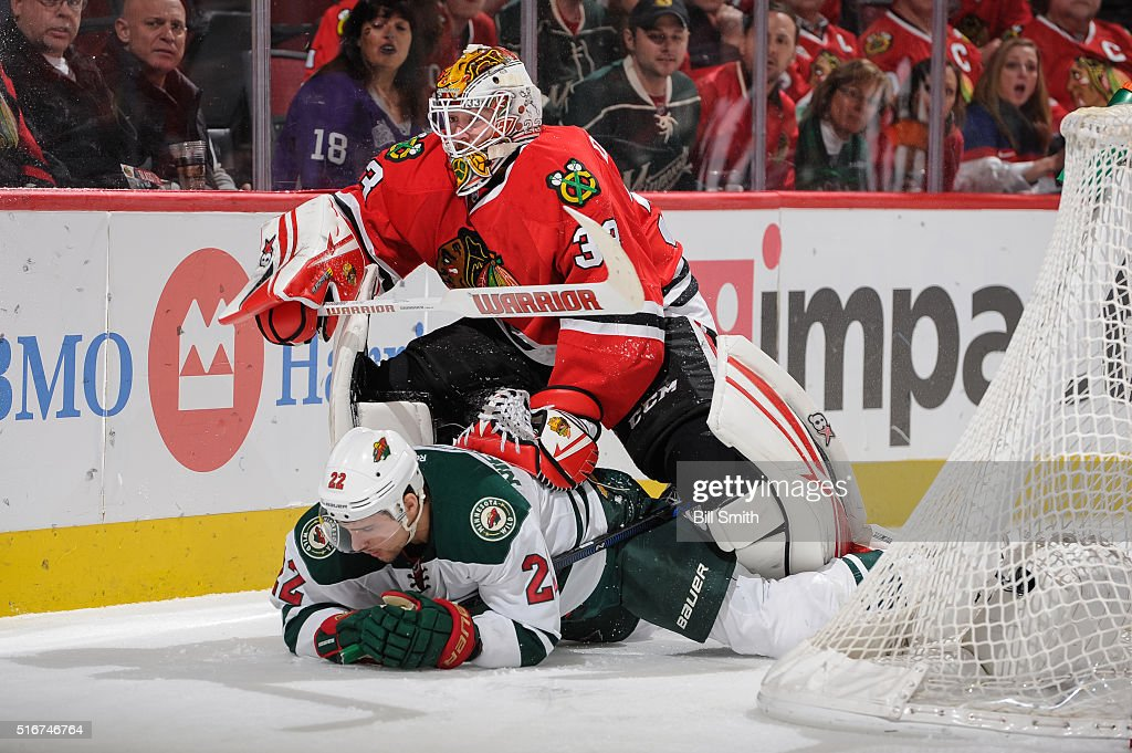 Goalie Scott Darling of the Chicago Blackhawks pushes down Nino Niederreiter of the Minnesota Wild in the first period of the NHL game at the United...