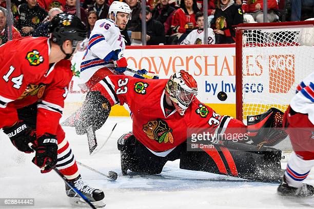 Goalie Scott Darling of the Chicago Blackhawks watches the puck while guarding the net as Marek Hrivik of the New York Rangers skates in the...