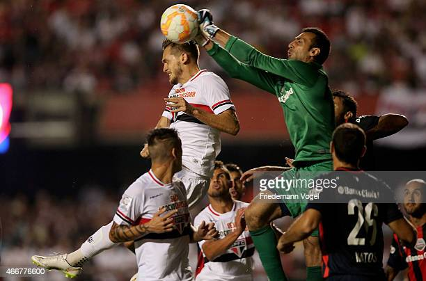 Goalie Sebastian Torrico of San Lorenzo battles for the ball with Rafael Toloi of Sao Paulo during a match between Sao Paulo and San Lorenzo as part...