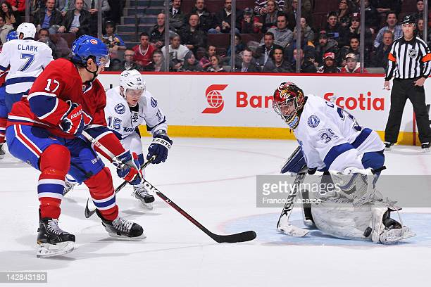 Goalie Sebastien Caron of the Tampa Bay Lightning makes a pad save as Chris Campoli of the Montreal Canadiens and Tampa Bay's Brian Lee look for the...