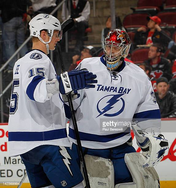 Goalie Sebastien Caron of the Tampa Bay Lightning talks with teammate Brian Lee as he skates onto the ice in an NHL hockey game against the New...