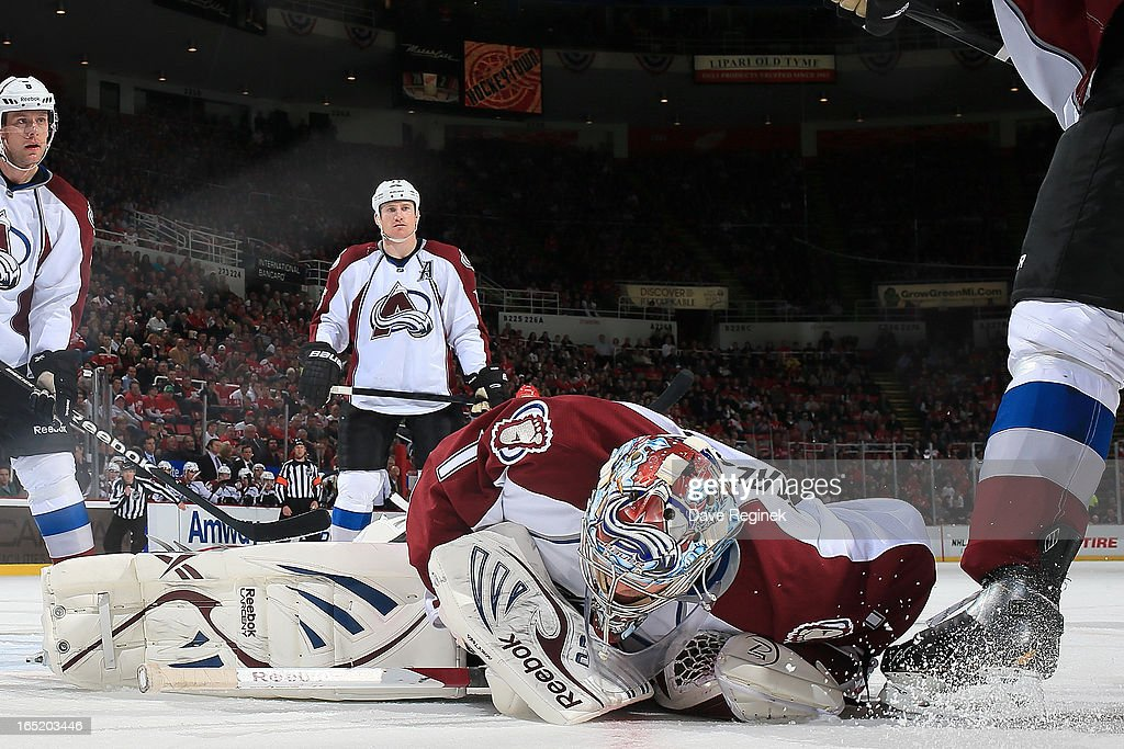 Goalie <a gi-track='captionPersonalityLinkClicked' href=/galleries/search?phrase=Semyon+Varlamov&family=editorial&specificpeople=6264893 ng-click='$event.stopPropagation()'>Semyon Varlamov</a> #1 of the Colorado Avalanche dives on top of the puck to cover it during a NHL game against the Detroit Red Wings at Joe Louis Arena on April 1, 2013 in Detroit, Michigan.