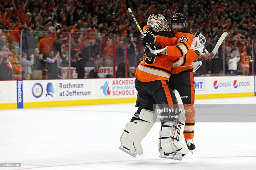 Goalie Steve Mason and teammate Jakub Voracek of the Philadelphia Flyers celebrate after defeating the Washington Capitals at Wells Fargo Center on...