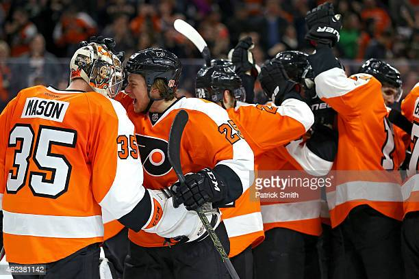 Goalie Steve Mason of the Philadelphia Flyers celebrates with teammate Ryan White after defeating the Arizona Coyotes at Wells Fargo Center on...