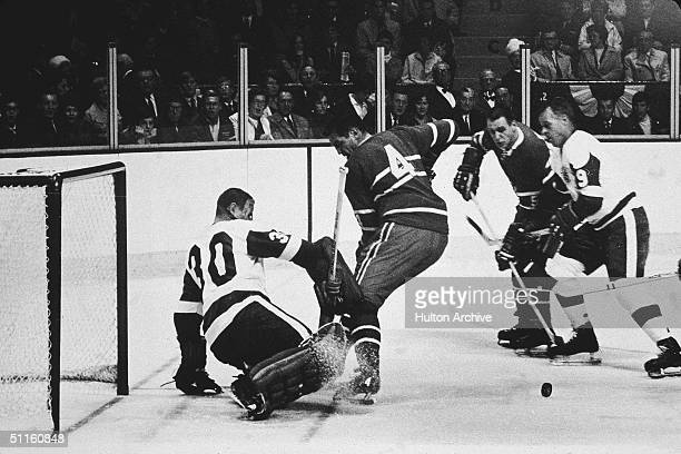 Goalie Terry Sawchuk of the Detroit Red Wings makes the save on the shot by Jean Beliveau of the Montreal Canadiens as Gordie Howe of the Red Wings...