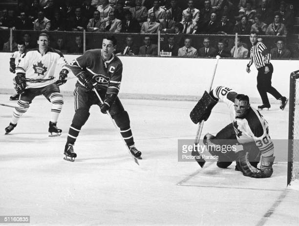 Goalie Terry Sawchuk of the Toronto Maple Leafs watches the puck while Jean Beliveau of the Montreal Canadiens waits in front of the net during Game...