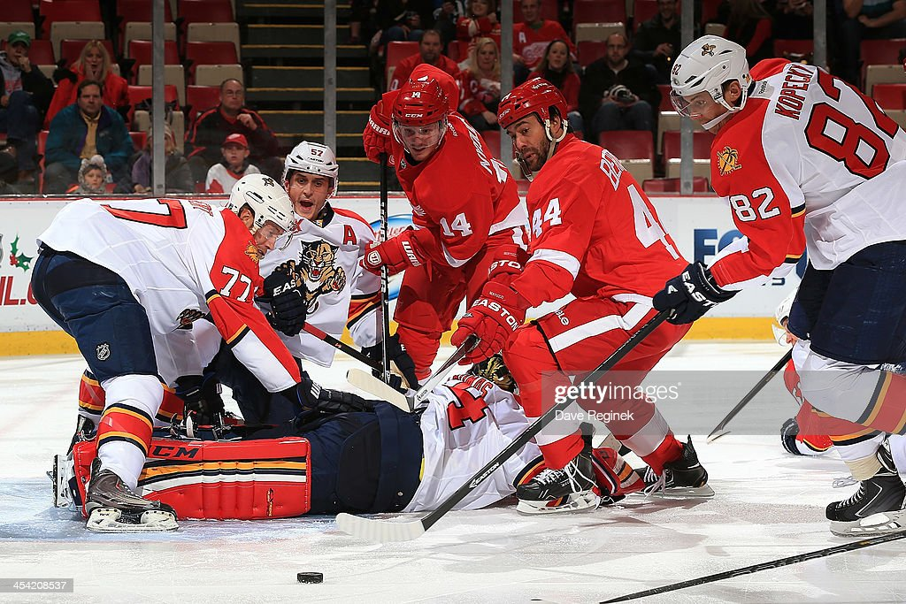 Goalie Tim Thomas #34 of the Florida Panthers thinks he has the puck covered while teammates Tom Gilbert #77, Marcel Goc #57 and Tomas Kopecky #82 as well as Gustav Nyquist #14 and Todd Bertuzzi #44 of the Detroit Red Wings all see the puck squirt free to the side of the net during an NHL game at Joe Louis Arena on December 7, 2013 in Detroit, Michigan.