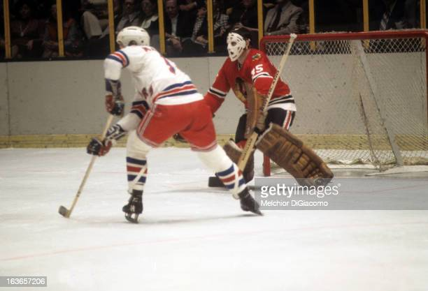 Goalie Tony Esposito of the Chicago Blackhawks defends the net as Bruce MacGregor of the New York Rangers looks for a pass circa 1973 at the Madison...
