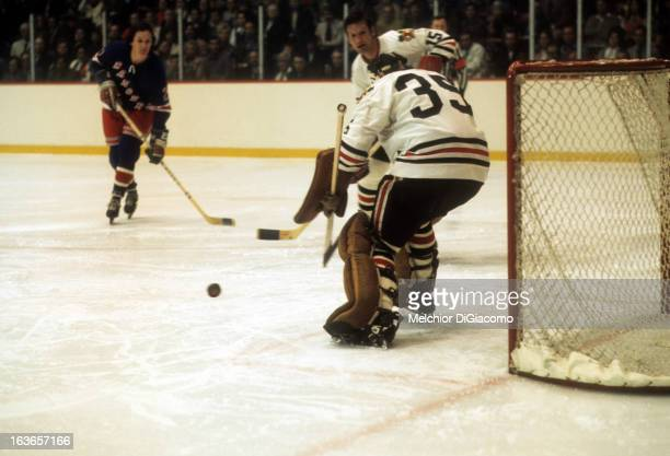 Goalie Tony Esposito of the Chicago Blackhawks goes for the puck during an NHL game against the New York Rangers circa 1973 at the Chicago Stadium in...