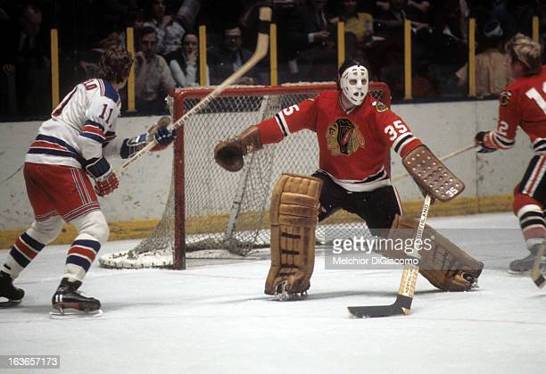 Goalie Tony Esposito of the Chicago Blackhawks makes the save as Vic Hadfield of the New York Rangers looks for the rebound circa 1973 at the Madison...