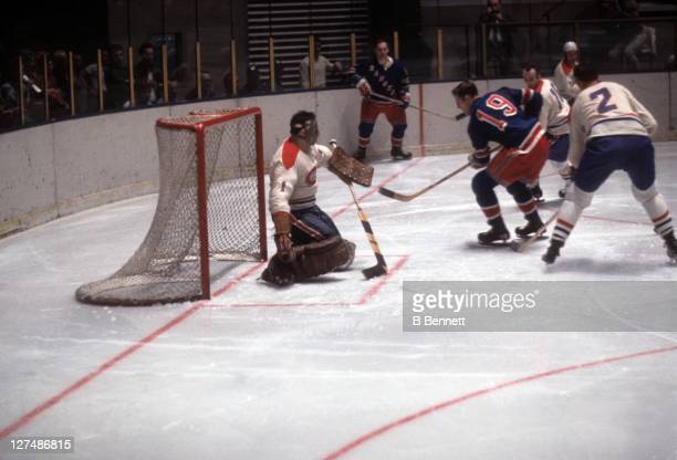 Goalie Tony Esposito of the Montreal Canadiens looks to make the save against Jean Ratelle of the New York Rangers as Jacques Laperriere of the...