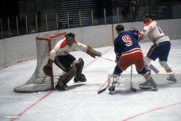 Goalie Tony Espostio of the Montreal Canadiens looks to make the save as his teammate Ted Harris looks to block out Reggie Fleming of the New York...