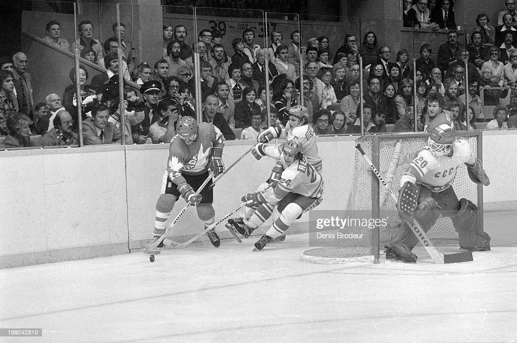 Goalie Vladislav Tretiak guards the goal while Vladimir Repnev and Zinetula Bilyaletdinov of the USSR skate behind the goal against Lanny McDonald of...