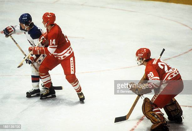 Goalie Vladislav Tretiak of the USSR defends the net as teammate Zinetula Bilyaletdinov battles with Neal Broten of Team USA during an 1980...