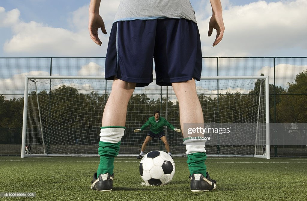 Goalie waiting and player with ball in front of goal post, rear view, low section : Stock Photo