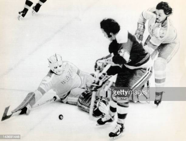 Goalie Yves Archambault of the Vancouver Blazers looks to block the shot by Serge Bernier of the Quebec Nordiques as defenseman Irvin Spencer looks...