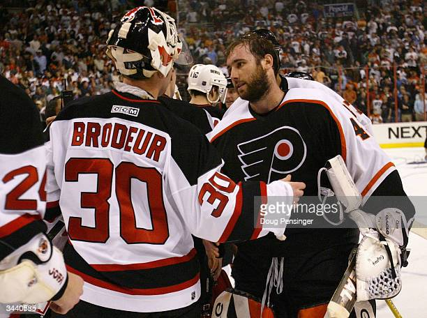 Goalies Martin Brodeur of the New Jersey Devils and Robert Esche of the Philadelphia Flyers shake hands following Game 5 as the Flyers defeated the...
