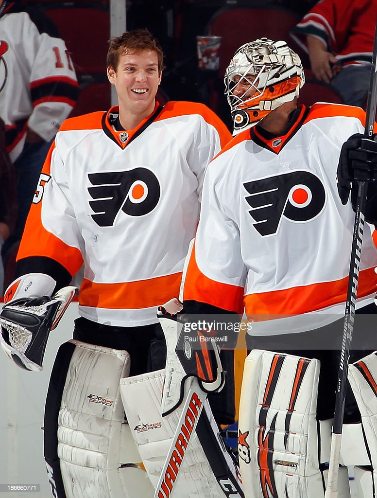 Goalies Steve Mason #35 and Ray Emery #29 of the Philadelphia Flyers skate off the ice smiling after a 1-0 shutout by Emery against the New Jersey Devils in an NHL hockey game at Prudential Center on November 2, 2013 in Newark, New Jersey.
