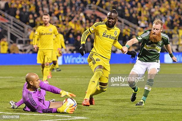 Goalkeeper Adam Kwarasey of the Portland Timbers slides in to take control of the ball as Kei Kamara of the Columbus Crew SC and Nat Borchers of the...