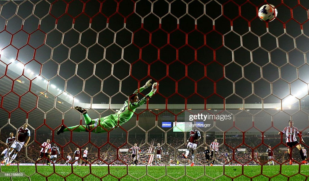 Goalkeeper Adrian of West Ham dives in vain as <a gi-track='captionPersonalityLinkClicked' href=/galleries/search?phrase=Adam+Johnson+-+Soccer+Player&family=editorial&specificpeople=6720094 ng-click='$event.stopPropagation()'>Adam Johnson</a> (2nd L) of Sunderland scores his team's goal during the Barclays Premier League match between Sunderland and West Ham United at the Stadium of Light on March 31, 2014 in Sunderland, England.