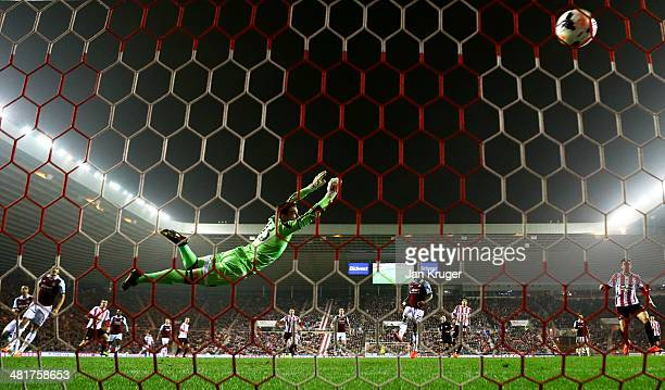 Goalkeeper Adrian of West Ham dives in vain as Adam Johnson of Sunderland scores his team's goal during the Barclays Premier League match between...