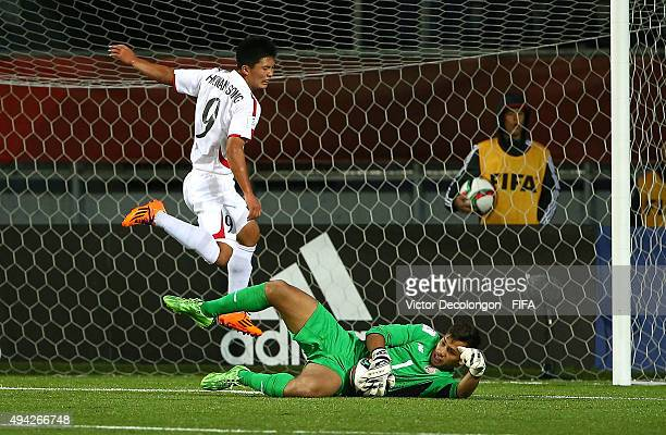 Goalkeeper Alejandro Barrientos of Costa Rica makes a save as Han Kwang Song of Korea DPR avoids contact during the Costa Rica v Korea DPR Group E...
