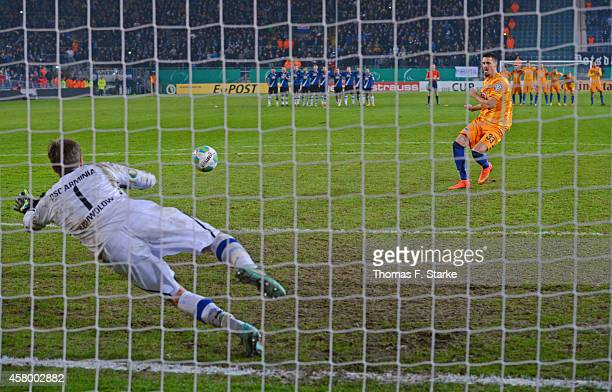 Goalkeeper Alexander Schwolow of Bielefeld saves a penalty by Sandro Wagner of Berlin during the DFB Cup match between Arminia Bielefeld and Hertha...