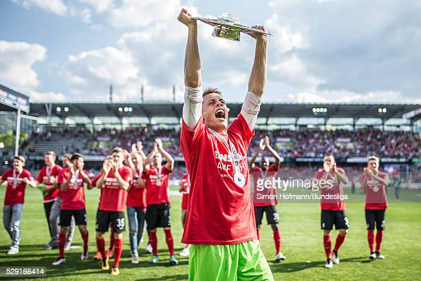 Goalkeeper Alexander Schwolow of Freiburg celebrates with the trophy after the Second Bundesliga match between SC Freiburg and 1 FC Heidenheim at...