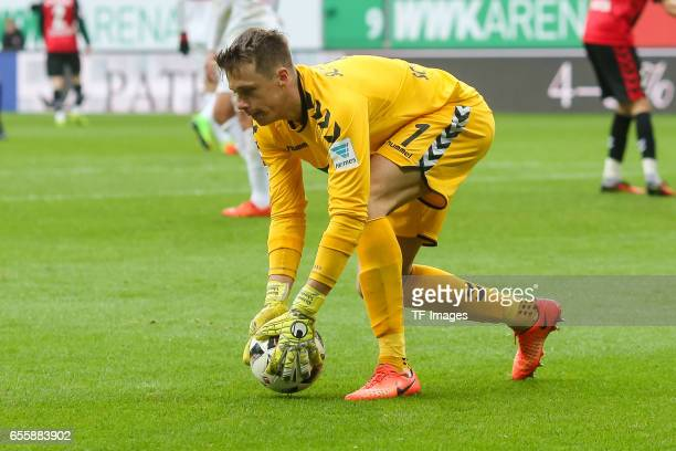 Goalkeeper Alexander Schwolow of Freiburg controls the ball during the Bundesliga match between FC Augsburg and SC Freiburg at WWK Arena on March 18...
